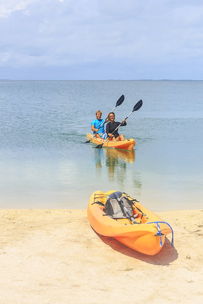 A Couple Arriving At The Beach In A Kayak, Saint Georges Caye Resort, Belize City, Belize