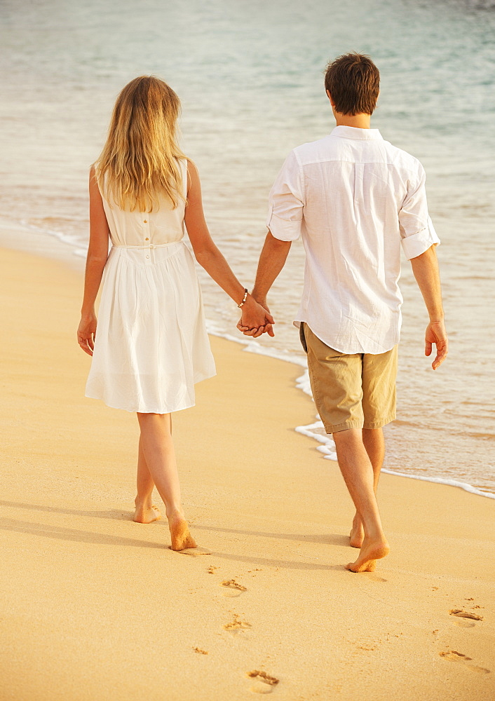 Young Couple In Love, Attractive Man And Woman Enjoying Romantic Walk On The Beach At Sunset Holding Hands