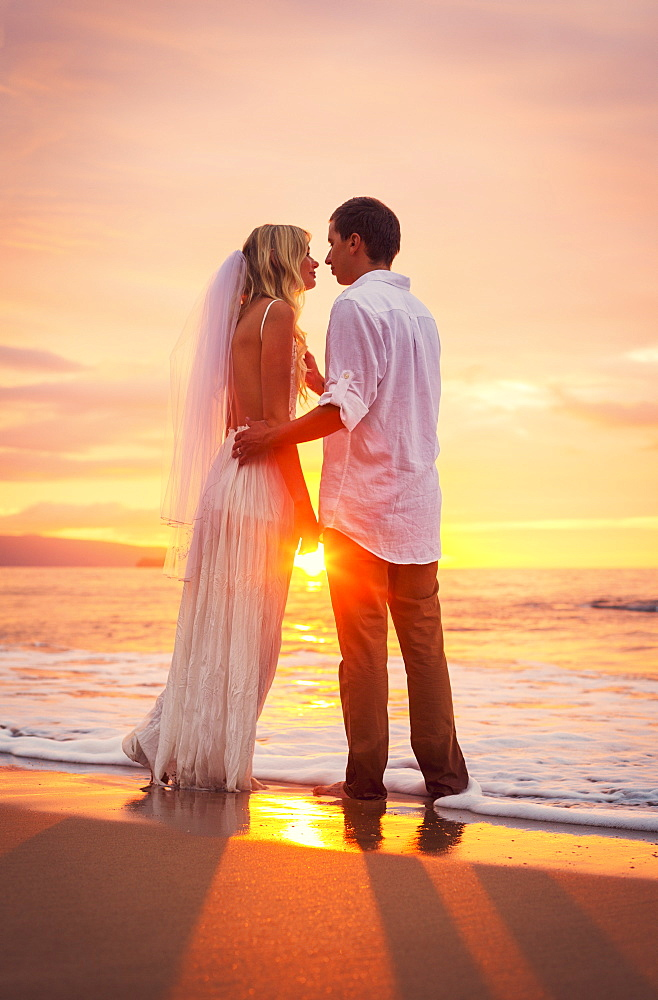 A Married Couple, Bride And Groom, At Sunset On A Beautiful Tropical Beach
