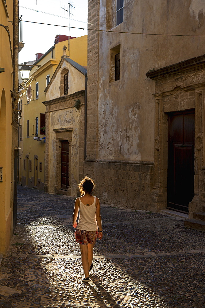 Girl Walking Down A Cobblestone Alley Between Buildings, Alghero, Sardinia, Italy