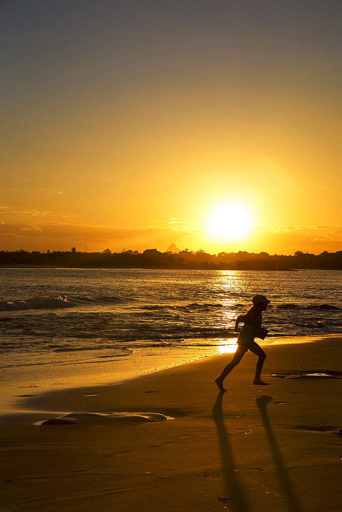 Silhouette Of A Child Running On A Beach At Sunset, Caloundra, Queensland, Australia