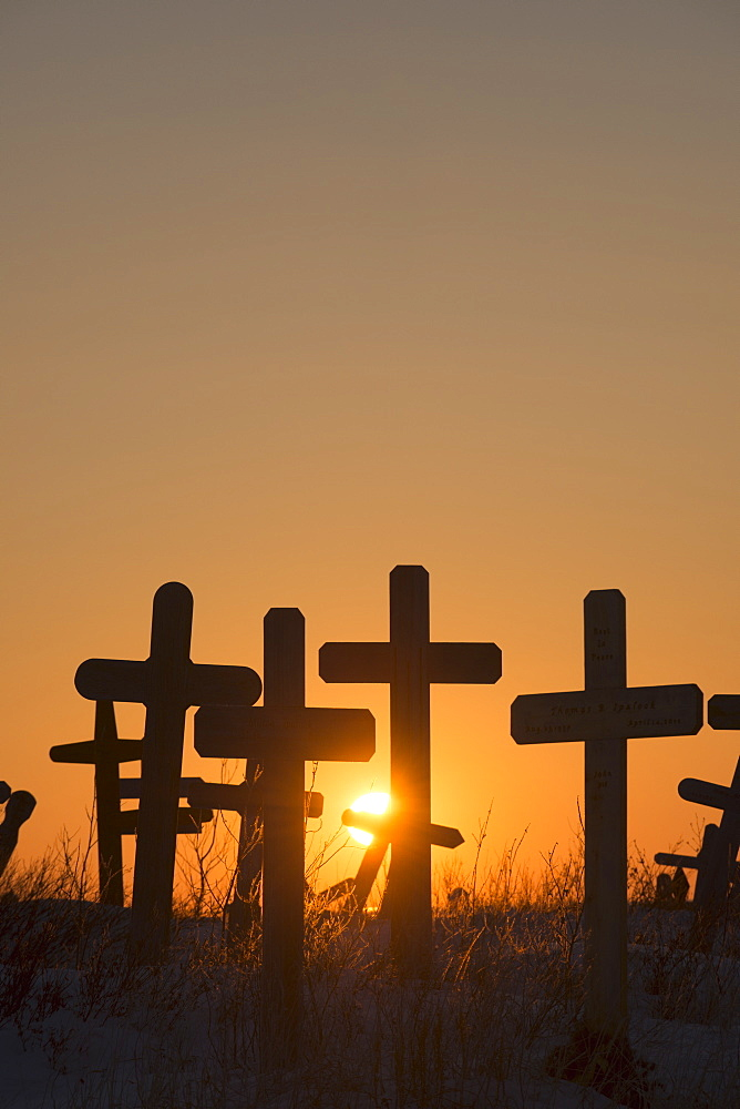A Setting Sun Shines Through Crosses At Cemetery Hill In Kotzebue, Alaska.