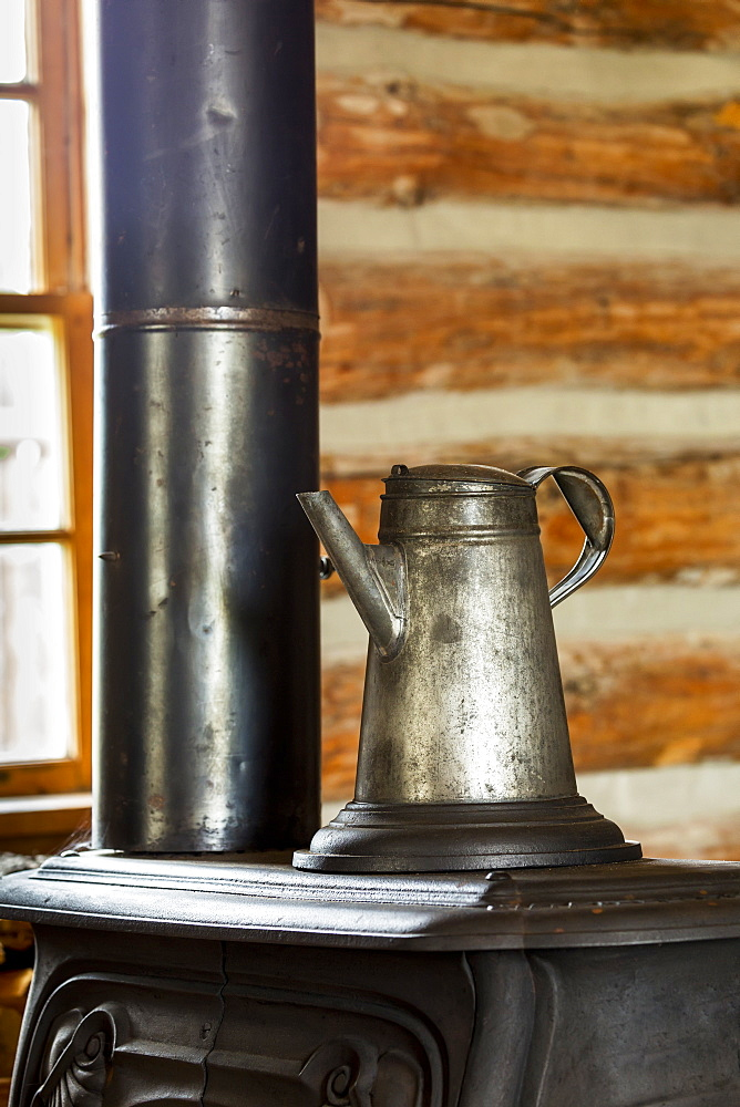 Close Up Of An Old Metal Coffee Pot On Top Of An Old Cast Iron Stove In Log Cabin With Window In The Background, South Of Maple Creek, Alberta, Canada