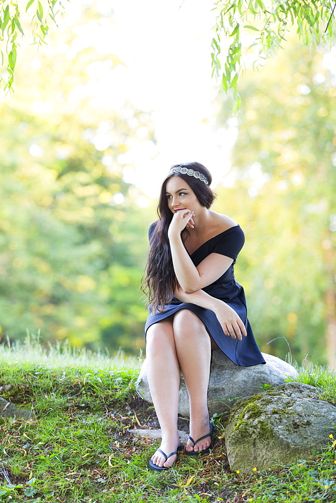 A Young Millennial Teenage Girl Poses For Her Grad Portraits In A Park With A Sparkling Headband And Modest Black Dress, Sitting On A Rock In The Forest Looking Thoughtful, Vancouver, British Columbia, Canada