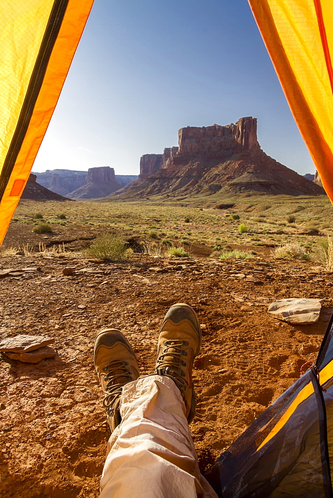 View Of A Camper's Feet Out Of A Tent Viewing Rock Cliffs, Canyonlands National Park, Utah, United States Of America