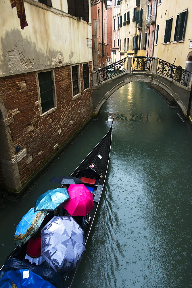 A Gondola Traveling Through A Canal On A Rainy Day With The Passengers Holding Umbrellas, Venice, Italy