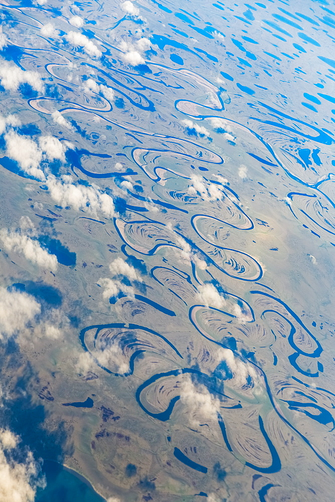 Aerial View Of Oxbow Rivers And Streams And Clouds Stretch Through The Tundra Landscape, North Slope, Alaska, United States Of America