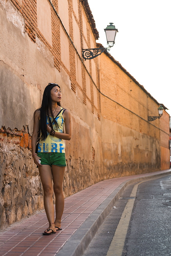 A Young Chinese Woman Walking Around Downtown Alcala De Henares, A Historical And Charming City Near To Madrid, Alcala De Henares, Spain