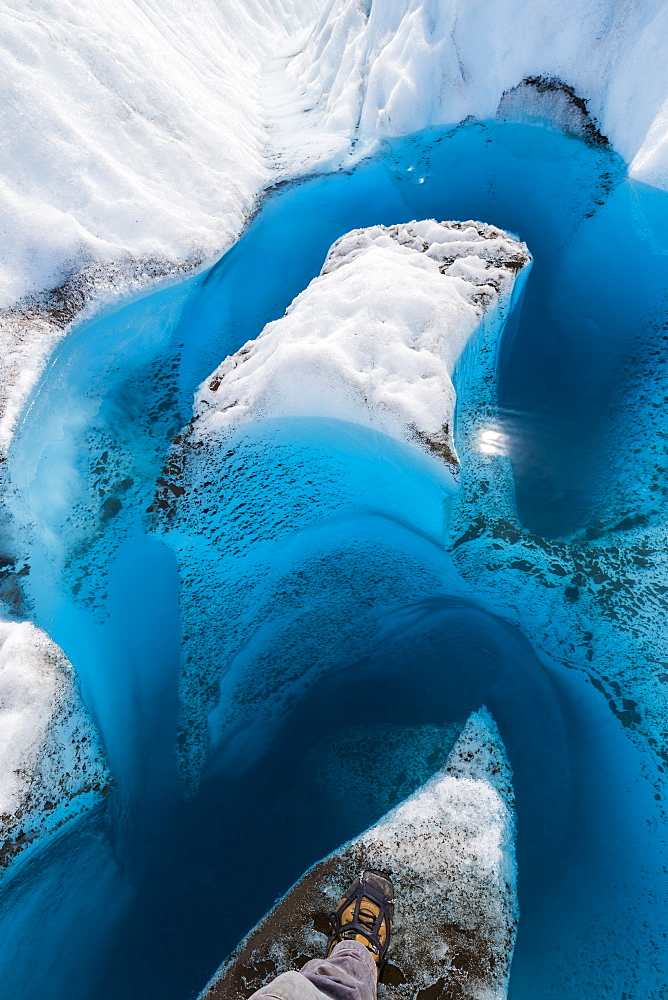 A hiker's boot showing the point of view looking down into the deep, blue meltwater of a glacier in Wrangell-St. Elias National Park, Alaska, United States of America