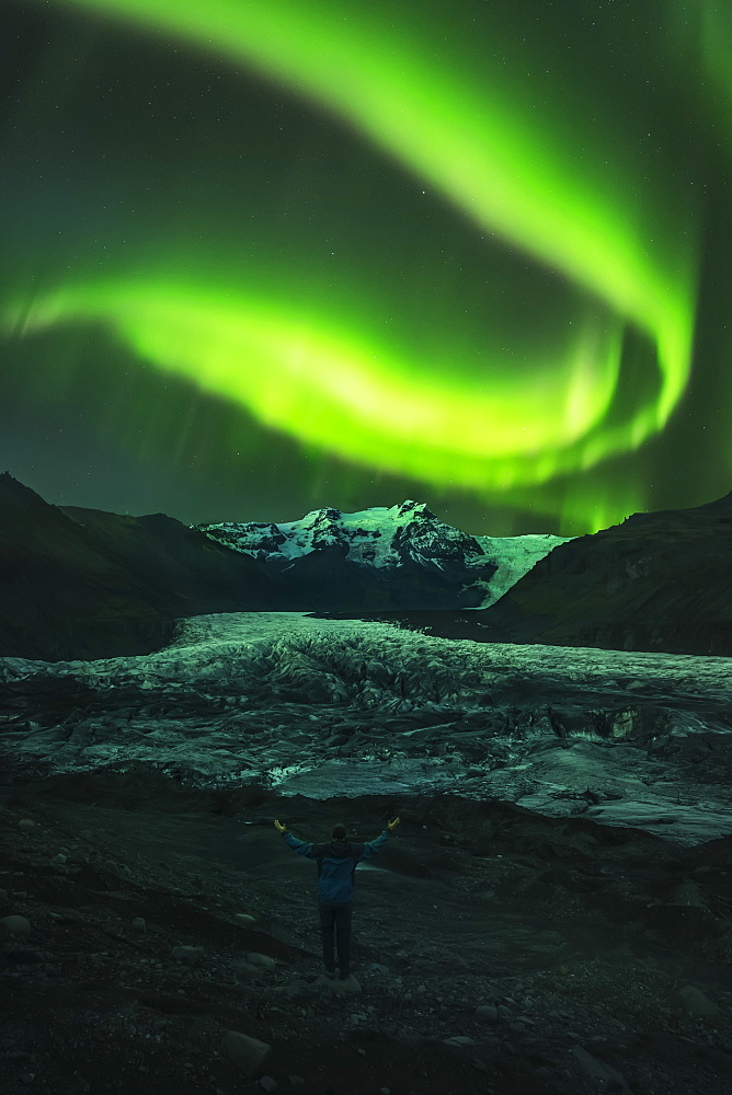 Person Standing With Their Arms Raised As If Orchestrating The Northern Lights, Iceland