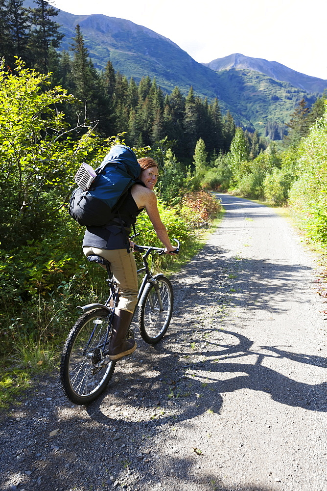 A Woman Mountain Bikes Down A Trail In A Forest With A Backpack, Alaska, United States Of America