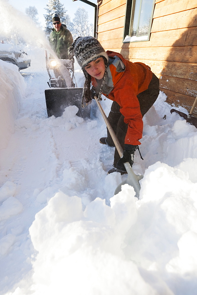 A Father And Daughter Removing Deep Snow At The Side Of Their House, Homer, Alaska, United States Of America