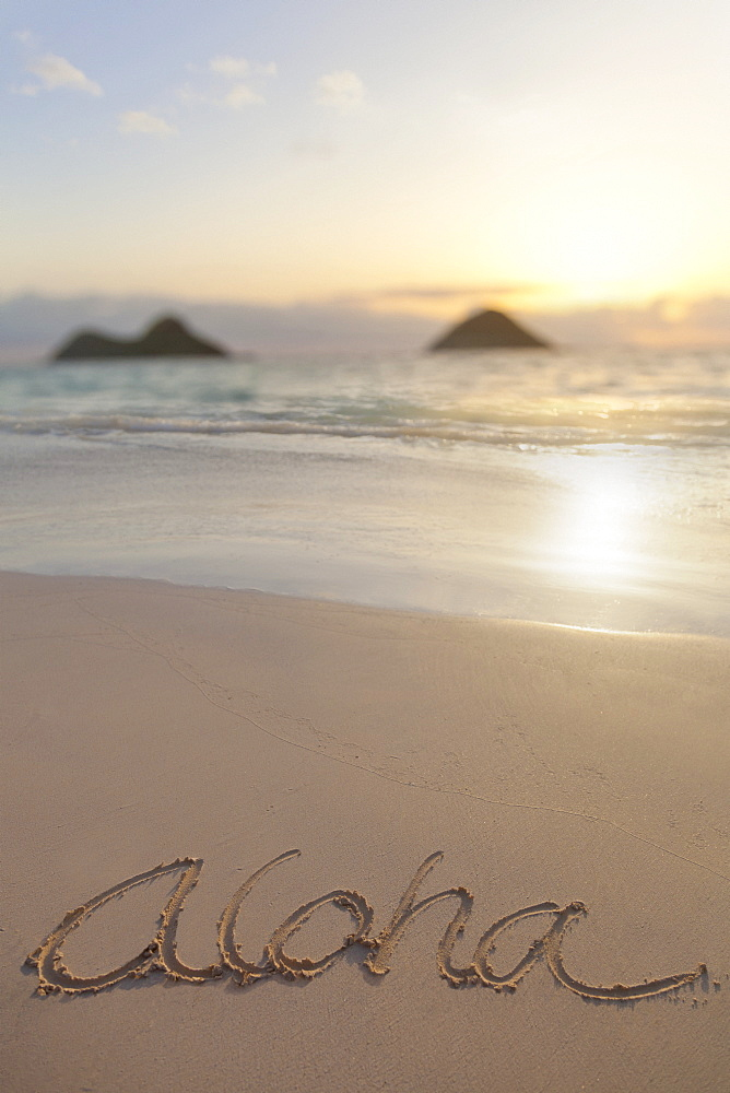 Aloha Written On The Sand On Lanikai Beach In Kailua With Mokulua Twin Islands In The Background At Sunrise, Honolulu, Oahu, Hawaii, United States Of America