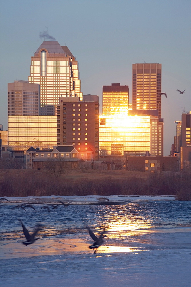 Calgary, Alberta, Canada; Bow River And Buildings Reflecting The Sun In Winter