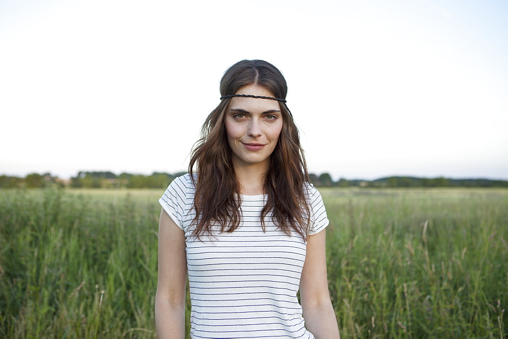 Profile of girl with hair band standing in secluded field
