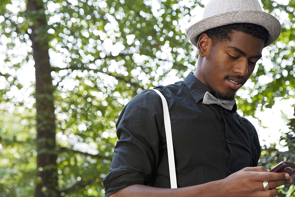 A black man dressed in bow tie and suspenders using a mobile phone