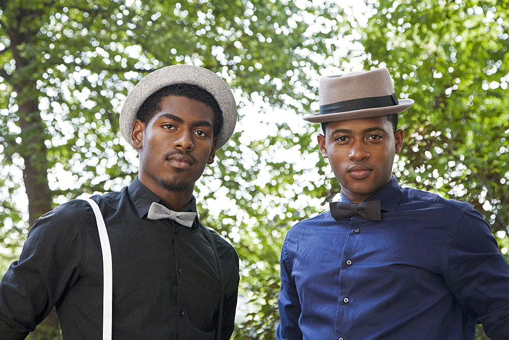 Two handsome young black men in bow ties and hats