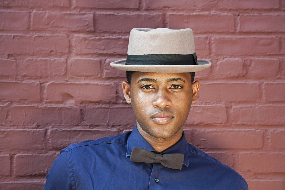A young black man wearing bow tie and hat, close-up