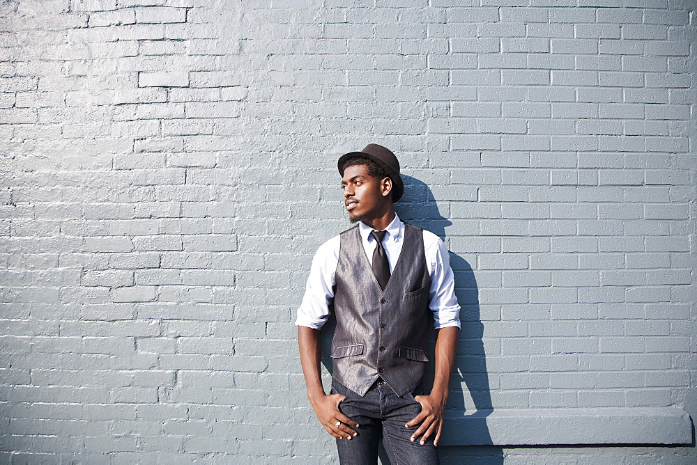 A young black man leaning against a brick wall - 1177-1029