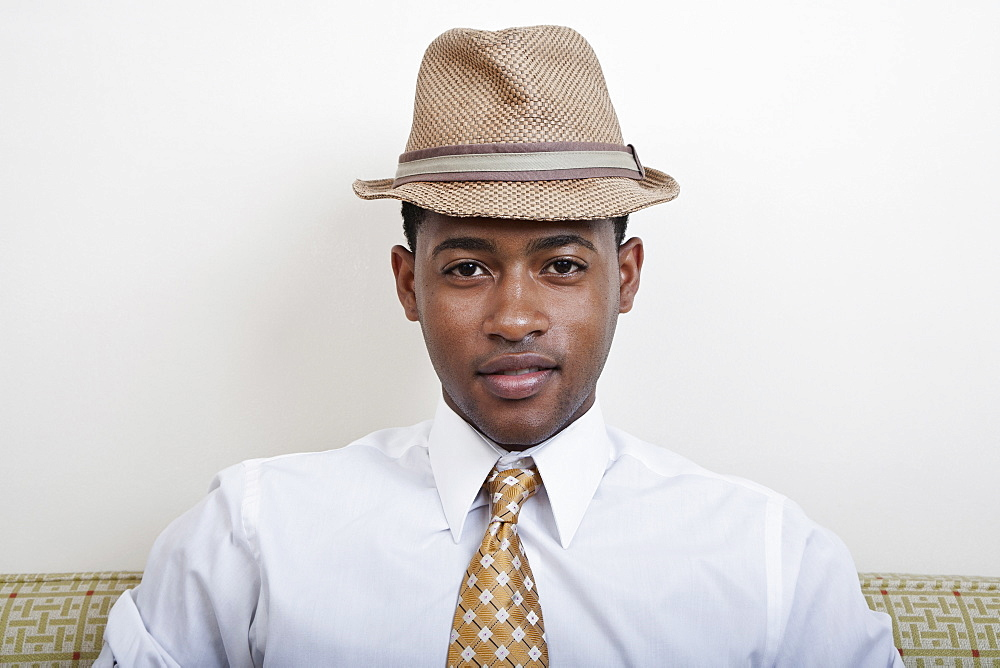 A young black man wearing a hat and tie
