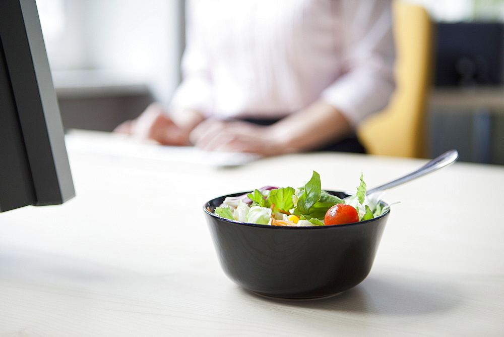 A salad on an office desk, in background a businesswoman typing