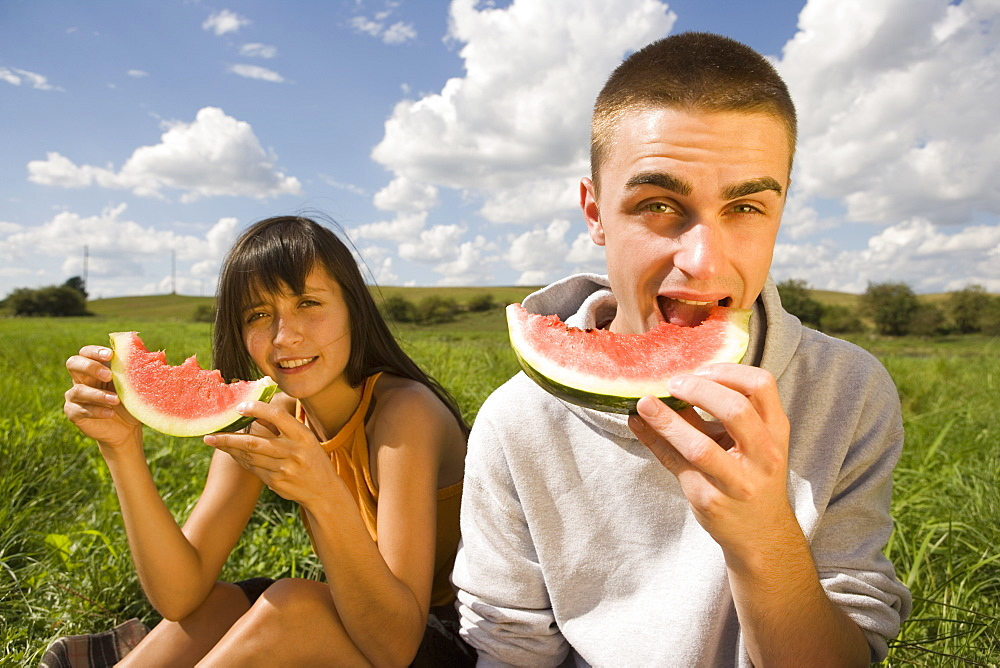 Young couple eating watermelon in field