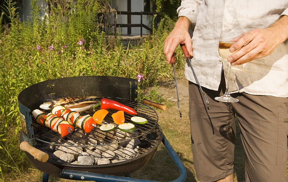 Man cooking fish and vegetable kebabs on a barbeque grill