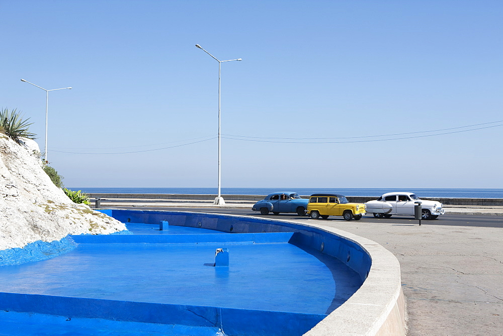 Classic cars moving by blue fountain against clear sky