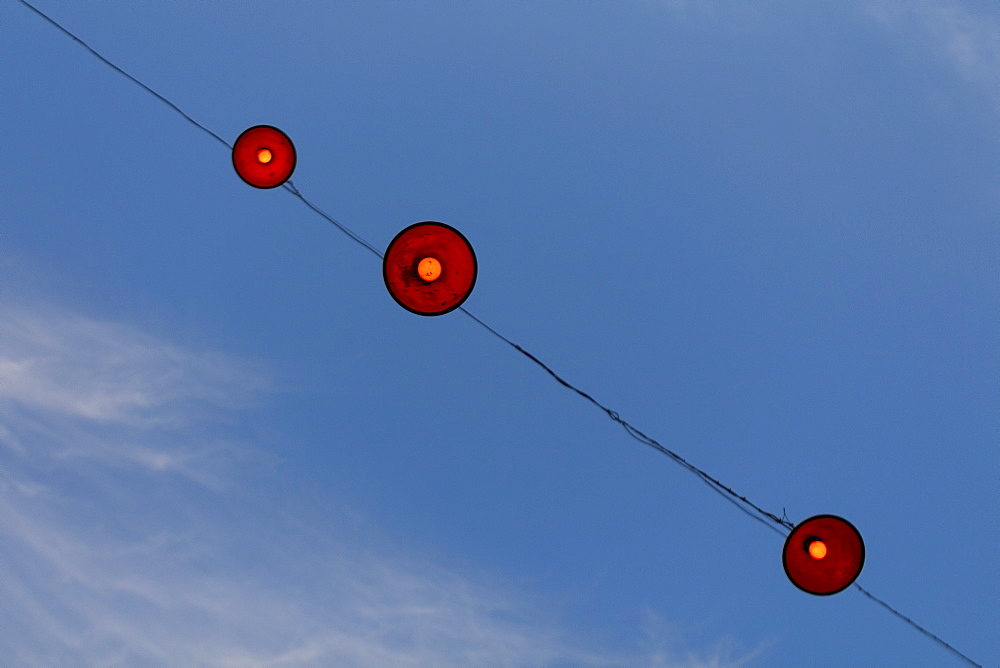 Low angle view of lamps hanging on cable against blue sky