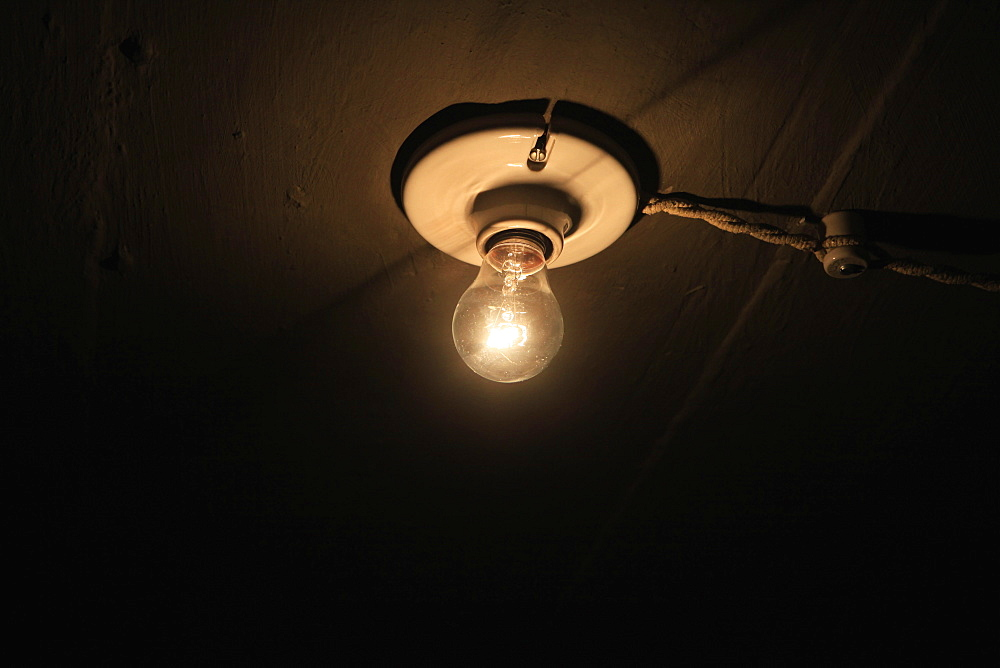 Low angle view of lit light bulb on ceiling
