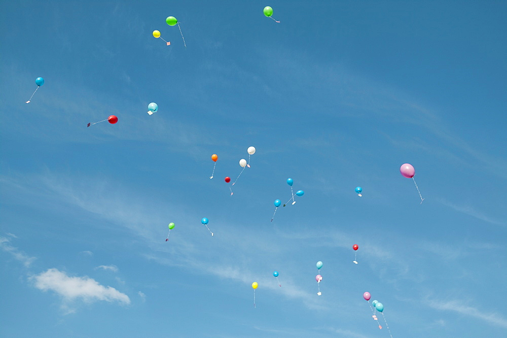 Low angle view of balloons with messages in mid-air against sky