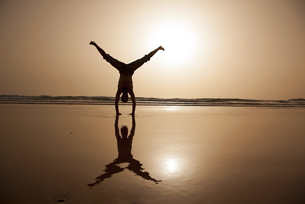 Full length of silhouette man performing handstand at beach