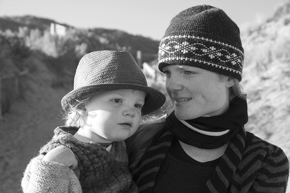 Smiling woman carrying son outdoors