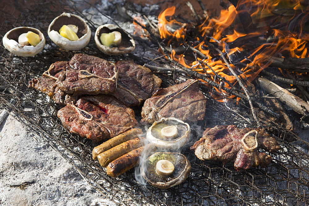High angle view of meat and mushrooms being grilled