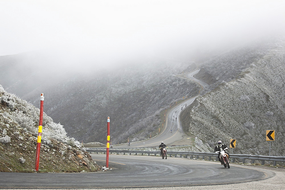 Motorcycle race on mountain road in foggy weather