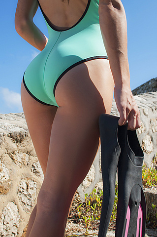 Midsection of sensuous woman in bodysuit holding diving flippers on beach