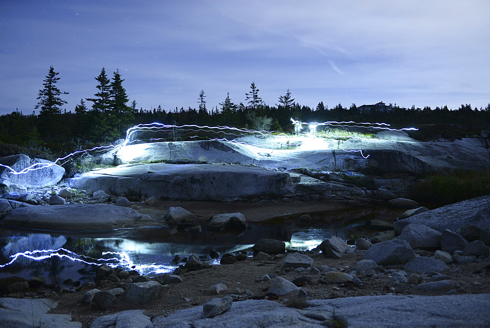 Light trails on rocky landscape