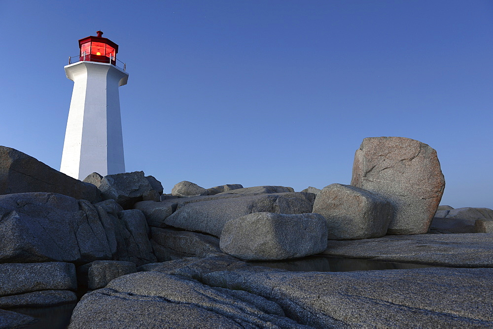 Low angle view of lighthouse on rocky landscape against clear blue sky