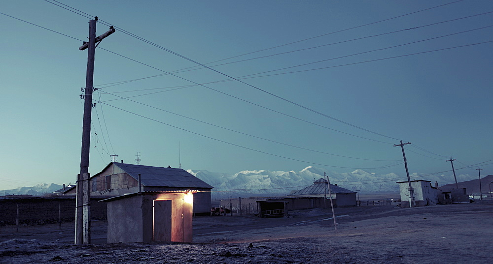 Electricity pylon and houses against sky at dusk, Kyrgyzstan