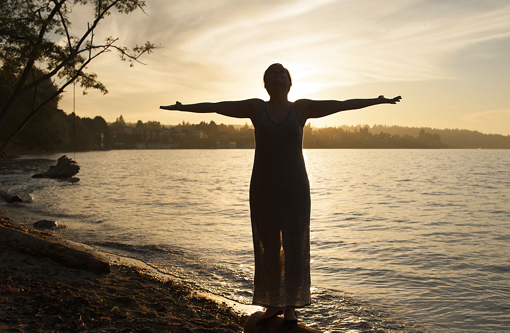 Full length of young woman standing with arms outstretched on lakeshore