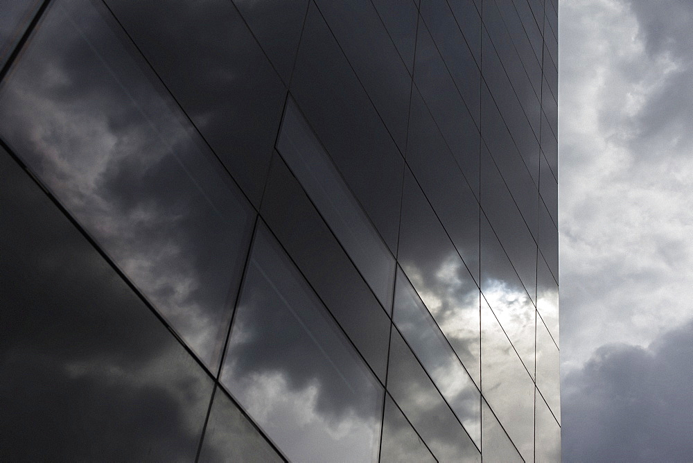 Low angle view of glass building against cloudy sky