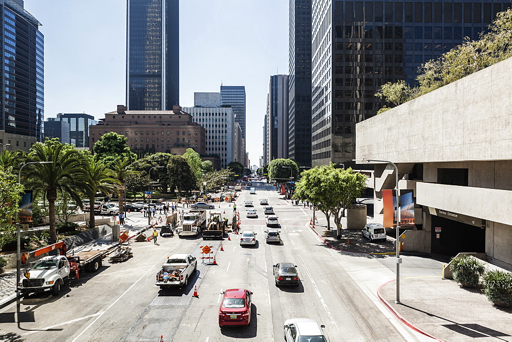 Cars on city street leading towards skyscrapers