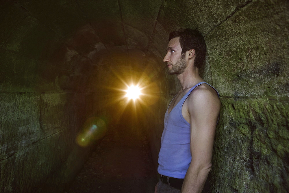 Side view of man leaning on tunnel wall