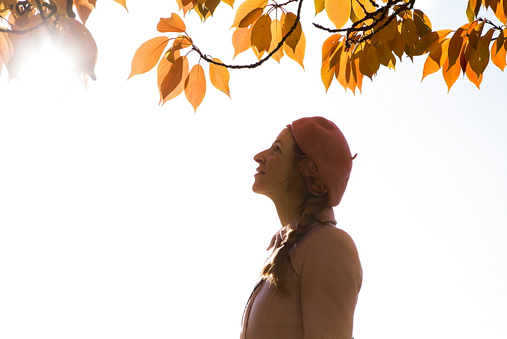 Side view of happy woman looking at tree during autumn