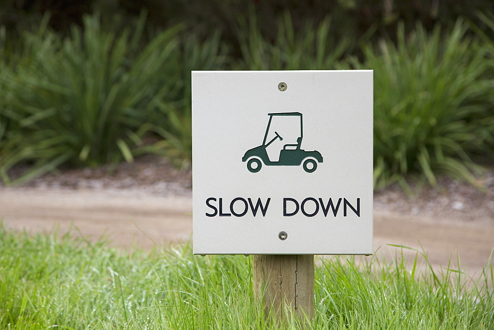 Slow down warning sign on field by dirt road
