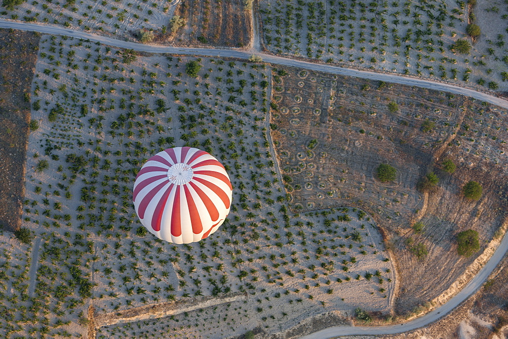 High angle view of striped hot air balloon flying over agricultural landscape