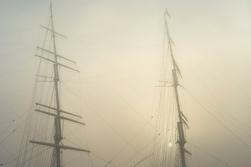 Low angle view of masts against sky in foggy weather