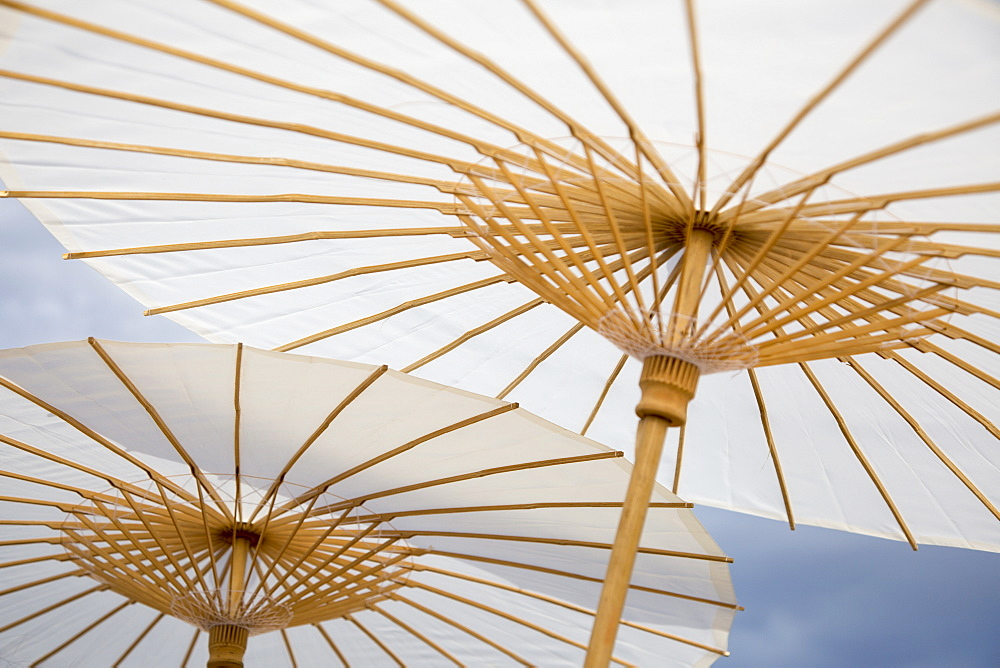 Low angle view of traditional parasols against sky
