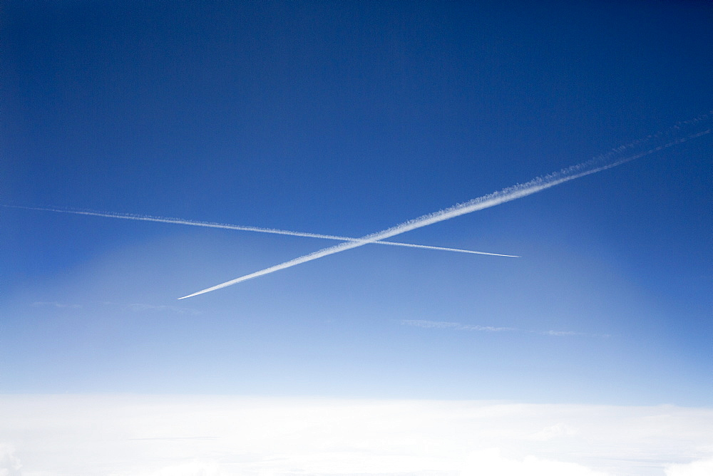 Low angle view of vapor trails in blue sky