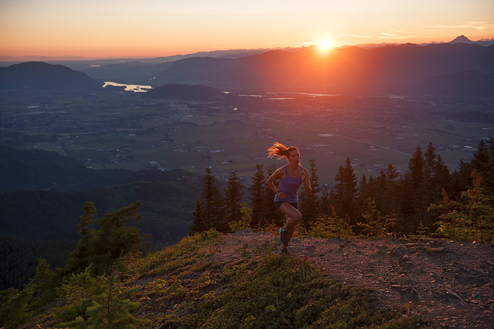Woman jogging on mountain path during sunrise